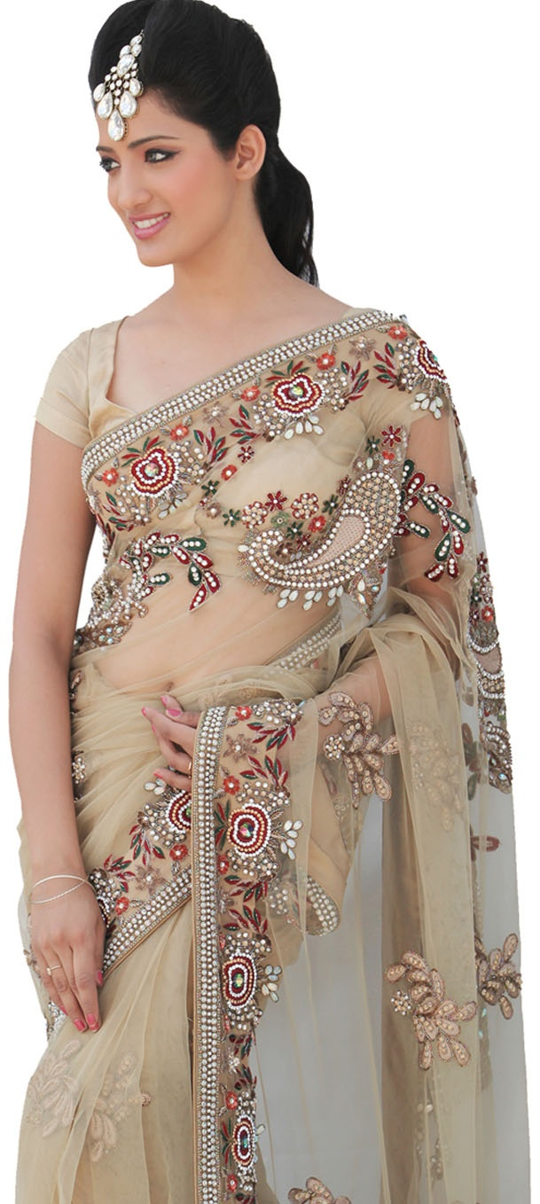 A beige gold net saree with heavy embroidery of resham paisley's and flowers all over, embellished with pearl Swarovski & cut - pipe.