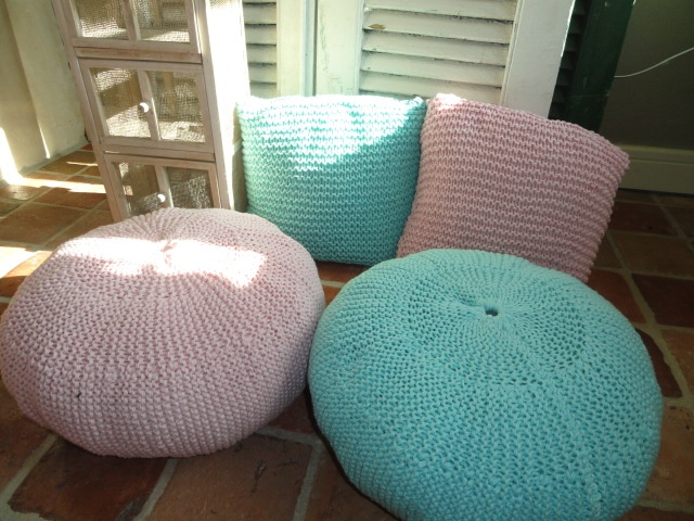 Hand-knitted poufs with matching pillows.