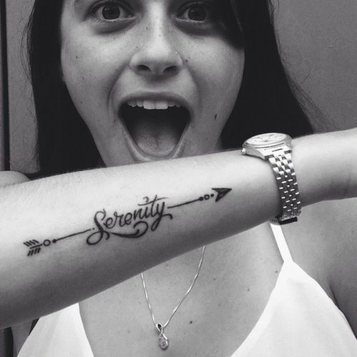Little forearm tattoo of an arrow crossing the word 'Serenity' on Eden.