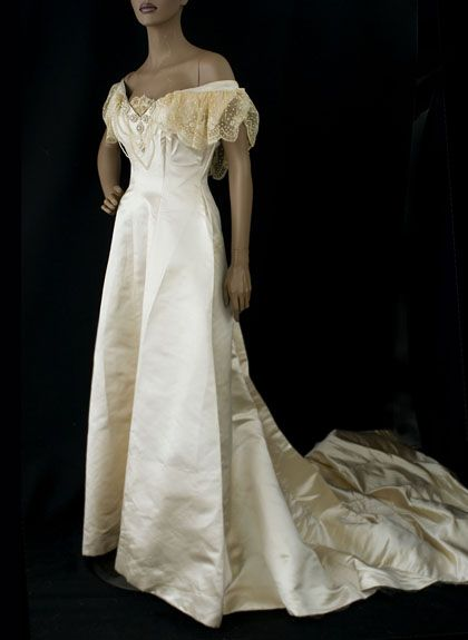 1908 satin wedding gown.  The skirt and train were left unadorned, emphasizing the quality of the ivory satin. The princess line seams mould the gown to the torso without adding bulk at the waist and hip. The deep neckline opening is trimmed with swags of faux pearls and lace flounces that forms partial sleeves.