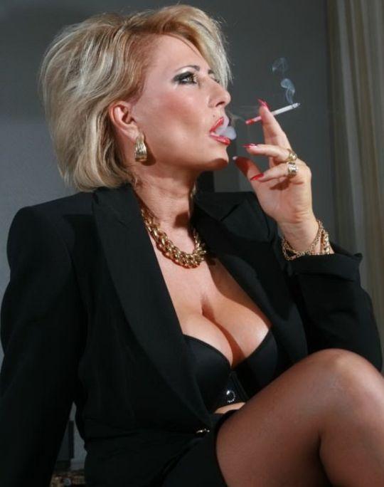 Mature woman smoking a cigarette stock photo