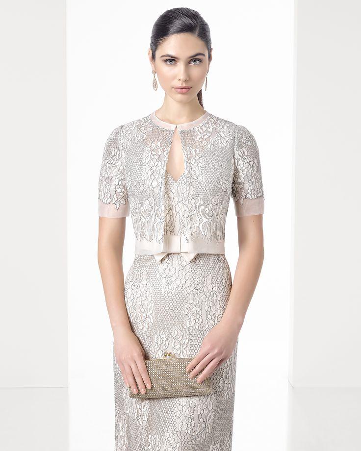 Vestido de fiesta largo silueta de encaje con escote y espalda en pico, manga corta y apertura trasera, en color beige y plata.