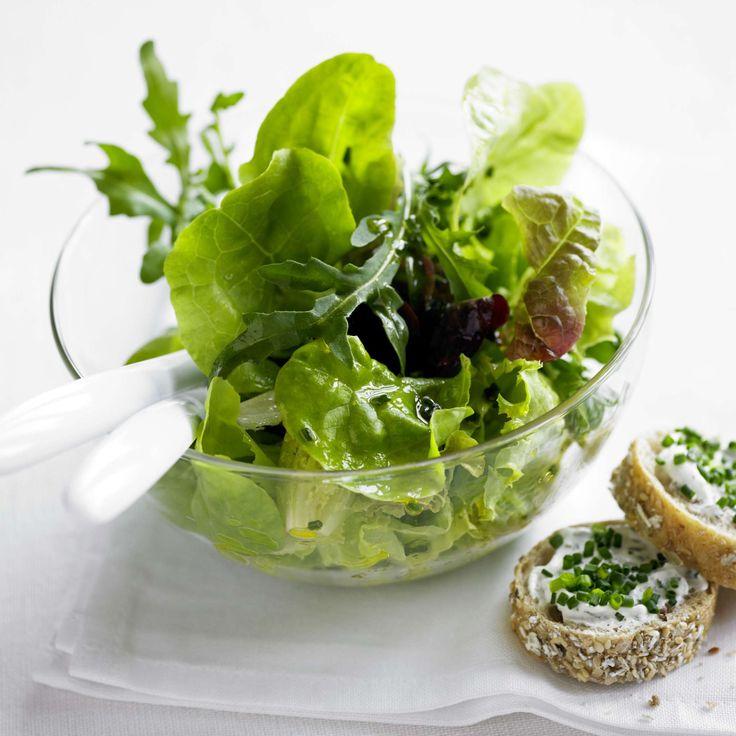 Salat mit Kräuterbaguette. Knackige Blattsalate mit einer Kräutervinaigrette, dazu dunkle Weizenbaguettescheiben mit Kräuterquark und frischem Schnittlauch – eine feine Sommerbeilage.