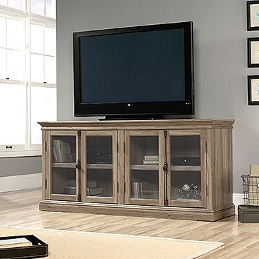 Accommodates up to an 80 in. TV weighing 135 lbs. or less. Framed, safety-tempered glass doors. Two adjustable shelves. Enclosed back panel with cord access. Salt Oak finish.