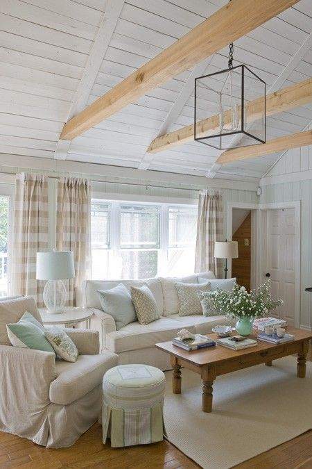 Laurentians Living Room  Soft shades of white add a relaxed feel... seating area has a subdued palette that evokes a laid-back, beachy vibe. Leaving the ceiling beams natural draws the eye upward, making a stunning pendant light the focal point.