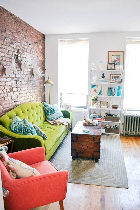 Exposed Brick Wall, Lime Green Sofa, Bubblegum Pink Chair, Wooden Trunk Coffee Table, White Painted Ceramic Animal Heads, Open Shelves, Colorful Throw Pillows, Lots of Natural Light // happy