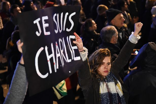 """A woman holds a banner that reads in French, """"I am Charlie"""" at the Old Harbor in Marseille"""