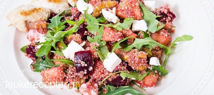 Gezonde salade van quinoa met rode biet, appel, walnoten en feta geserveerd met kipspiesjes