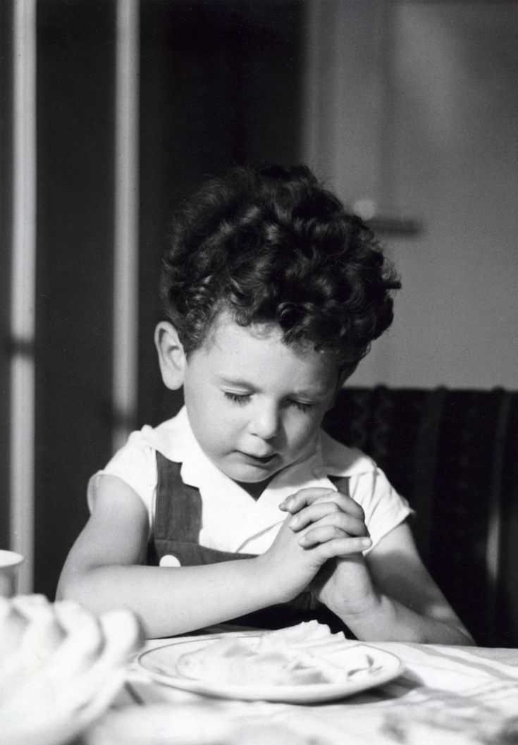 Een jongetje bidt voor het eten. Plaats onbekend, 1956.