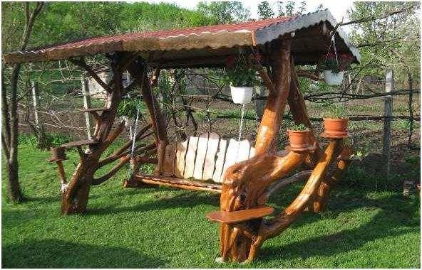 Romantisch houten schommel bankje, gemaakt met sloophout en boomstammen.
