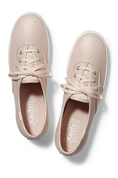 A classic Ked shoe with a twist. Metallic rose gold! This shoe features a soft textured canvas material with a lace up front and white border along the sole. Great with leggings or any denim! Get your