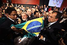 A man holds a flag surrounded by several people celebrating. In the background, photographers record the moment.