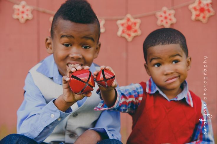Brothers holding Christmas ornaments