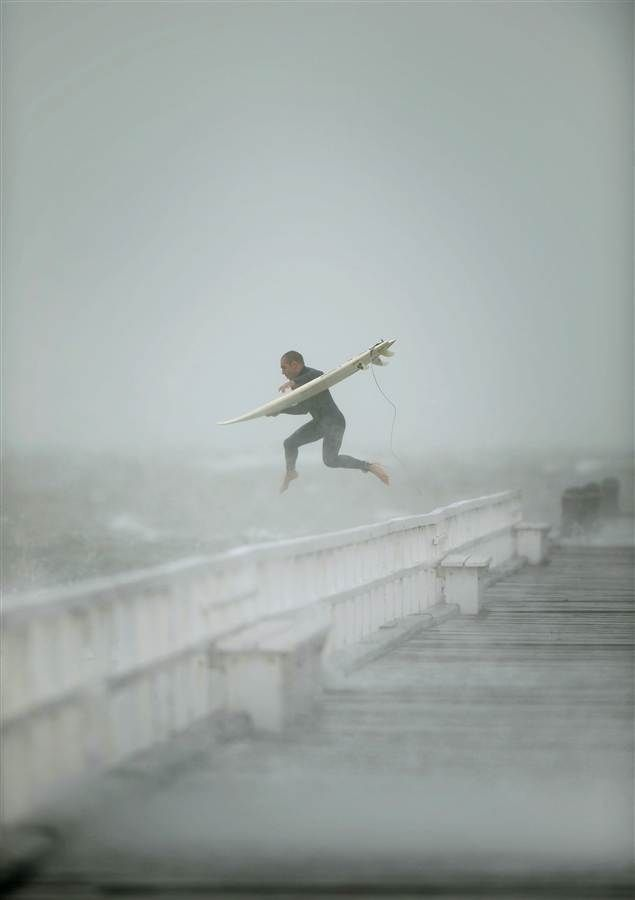 A surfer jumps off the pier into Port Phillip Bay to take advantage of the waves as a storm lashes the Melbourne, Australia area on 6/24/14.