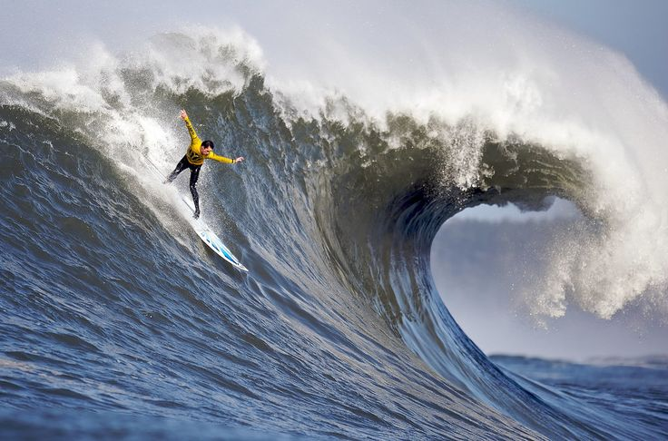 A surfer performing a late drop in ocean wave, Mavericks, California  Photo credit: Shalom Jacobovitz via Wikimedia Commons, Public Domain  en.wikipedia.org/wiki/List_of_surface_water_sports#/media...