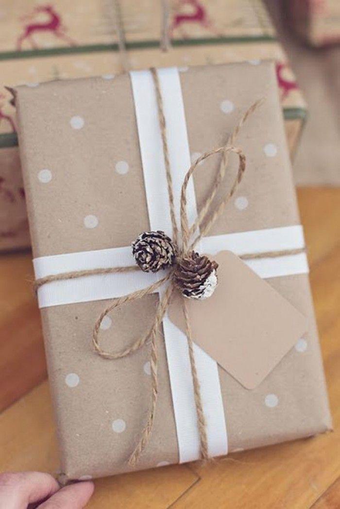 Cadeau inpakken met bruin papier met stippen, 2 lange stroken papier of lint, een stuk touw, paar kleine dennenappeltjes en eventueel een papieren cadeaulabel.