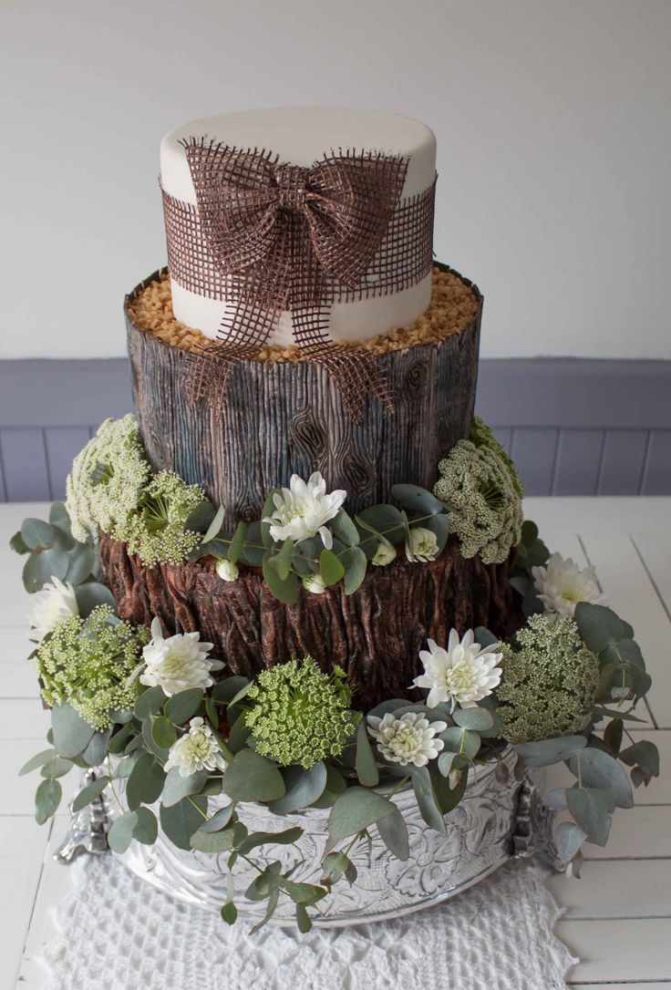 Woodland cake: lacy flowers, white chrysanthemums. Edible hessian bow.