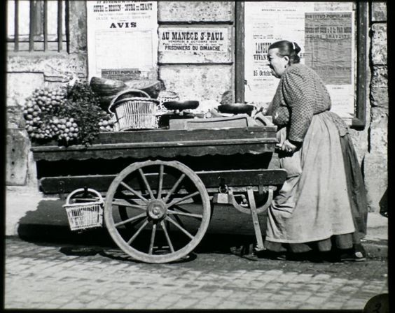 A vegatable seller with her cart & balance in the Paris streets in 1906. Behind adverts for drawing & singing lessons.: