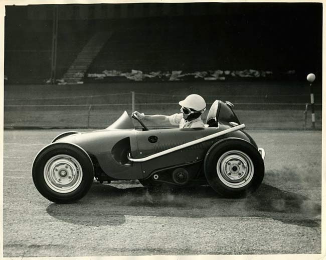 "Atom racing car The second photograph is a month later than the one shown above, dating to October 1955... ""Midget Racer undergoes trials. Essex: Wimbledon Speedway rider Cyril Brine leans out to see how high the front wheel will lift on a bend during trials of the Atom Car - claimed to be the smallest racing car in the world. Powered by a 500cc JAP speedway engine the car has been built by Wimbledon Speedway controller Ronnie Greene in conjunction with designer Sydney Allard, and it is…"