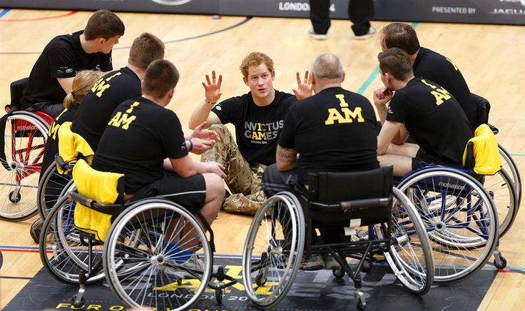 Part of the team Prince Harry talks with wheelchair-bound basketball players during the launch of the Invictus Games at the Queen Elizabeth Olympic Park in London on March 6, 2014. The Invictus Games for wounded, injured and sick service personnel will use the power of sport to inspire recovery, support rehabilitation and generate a wider understanding of those who serve the country.