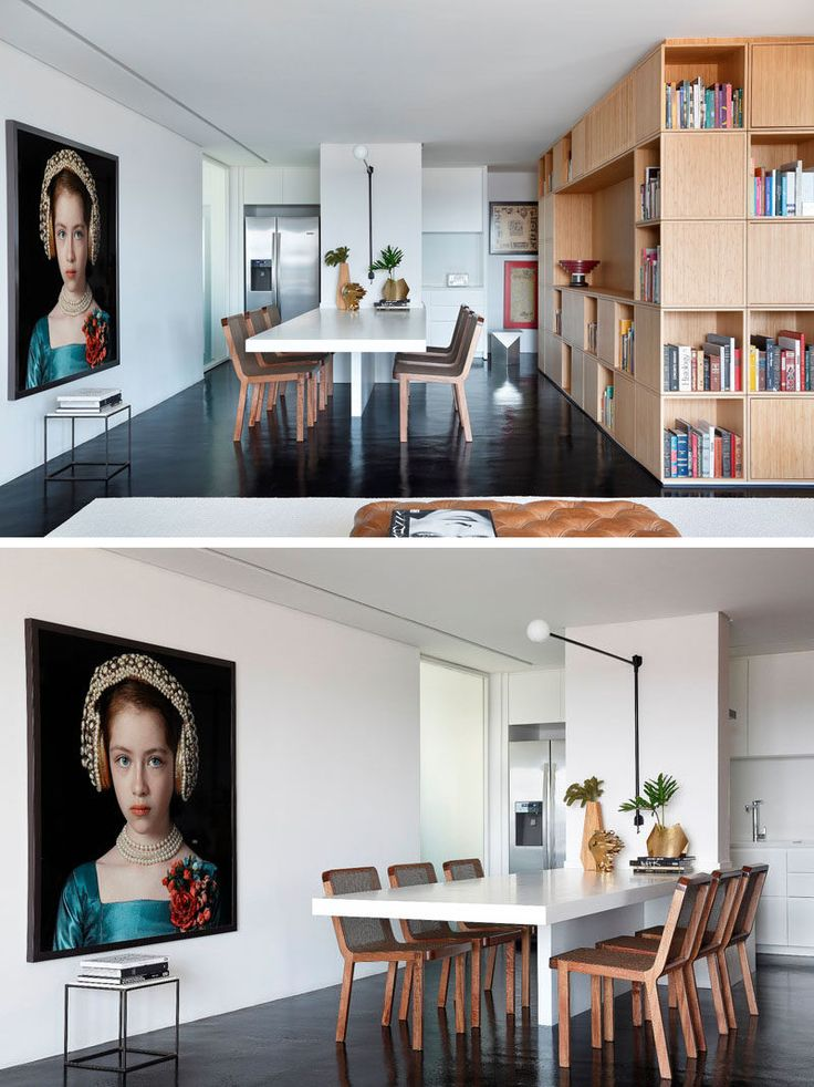 In this modern kitchen and dining area, a long white dining table is attached to a central wall, and the kitchen at the back of the dining room features all white cabinetry and stainless steel appliances.
