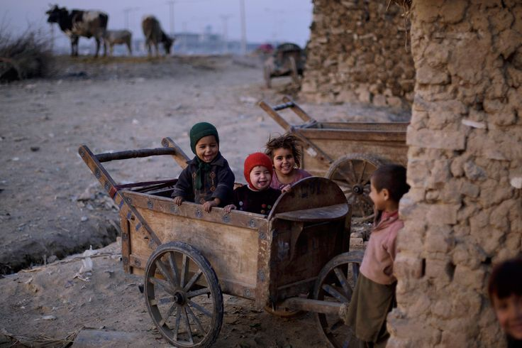 Pakistani children play in a wooden cart in a slum area on the outskirts of Islamabad. (Muhammed Muheisen/Associated Press)