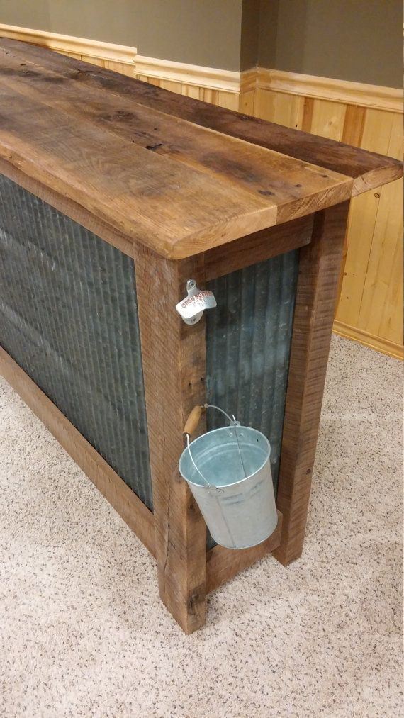 **THIS SPECIFIC ITEM HAS BEEN SOLD BUT I CAN BUILD ONE IN SIMILAR STYLE**  PLEASE MESSAGE ME FOR A FREIGHT SHIPPING QUOTE BEFORE PURCHASING  Rustic bar made from real reclaimed barnwood and corrugated metal roofing salvaged from an 80+ year old barn in central Ohio!  This piece is truly unique! It features solid oak barnwood and corrugated metal roofing construction complete with a very rustic and distressed bar top. Also includes a shelf on the inside and mounted bottle opener with bucket…