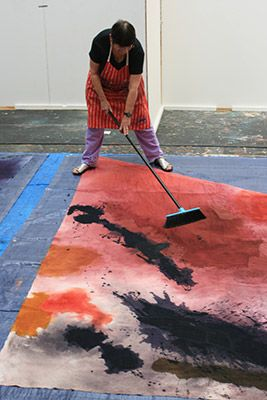 mary lloyd jones . working in the school of Art Studio using broom to manipulate dyes on cloth, 2011//