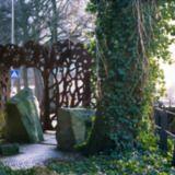 """Groningen. De tuin 'Een oase in de stad' is bedacht door beeldend kunstenaar Noud de Wolf. De Wolf maakte aan de voor- en achterkant van de tuin een hekwerk van cortenstaal. Het laat een decoratief patroon zien van gestileerde boomstammen, takken en gebladerte: """"een samengedrukt bos"""", zoals de kunstenaar zegt."""