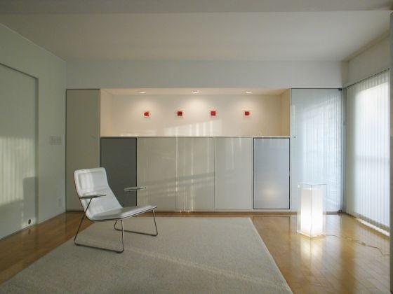 アートウォールのある壁面の反対側には、季節の変化や気分に応じて飾るものを変えていける〈現代の床の間〉のようなニッチが設けられている。ニッチの下の収納には、オーディオ機器とCDなどが納められている。また、右手に置かれたフロアライトは、この住まいのためにデザインされたもの。