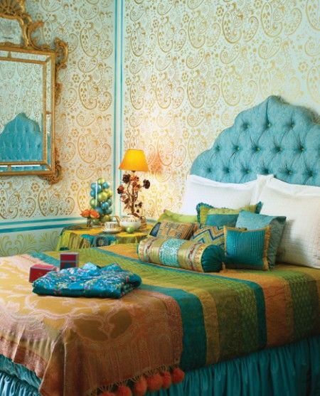 Create an exotic escape for your guests with an Indian-themed room.  Yards of sumptuous silk, bedding and pillows were imported from India to create this alluring space. The temple-shaped tufted headboard and stenciled paisley walls were created by designer Holly Dyment.