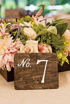 I think it would look good to just stencil and spray paint the table numbers onto wood tabs.