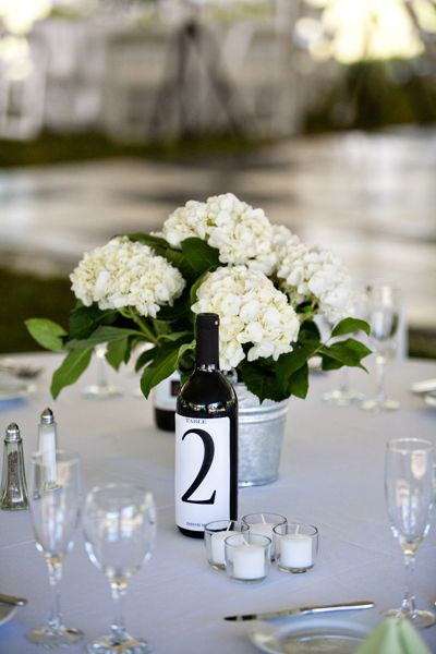 wine bottle table number and rustic flower centerpiece. Could be cute to do champagne for the toast not wine?