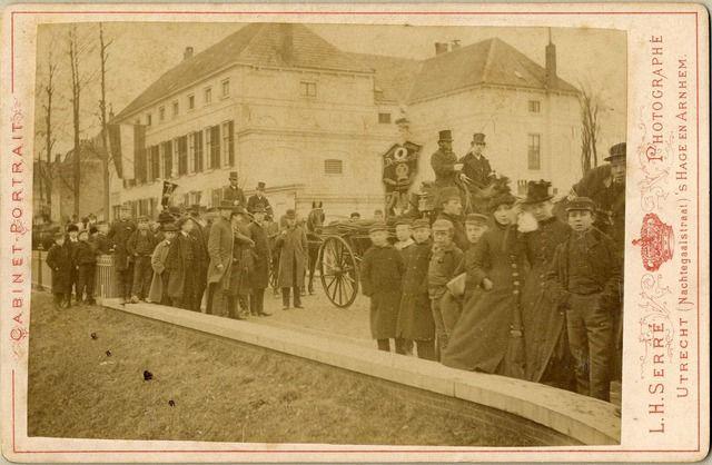 Afbeelding van leden van de Rederijkerskamer Demosthenes in de optocht ter gelegenheid van de viering van de 70e verjaardag van koning Willem III, in de Biltstraat te Utrecht; op de achtergrond het hoofdgebouw van de Rijksveeartsenijschool (Biltstraat Wijk I 69) te Utrecht.  N.B. Het adres Biltstraat Wijk I 69 is in 1879 gewijzigd in Biltstraat 110 en omstreeks 1895 in Biltstraat 172. 19-02-1887