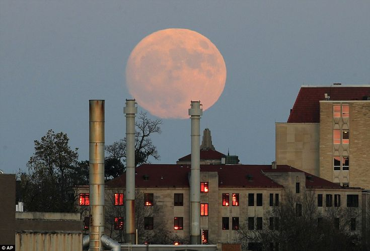 The moon's distance from Earth varies because it is in an egg-shaped, not circular, orbit around the planet. A photographer captured the moon rising beyond the University of Kansas in Lawrence, Kansas