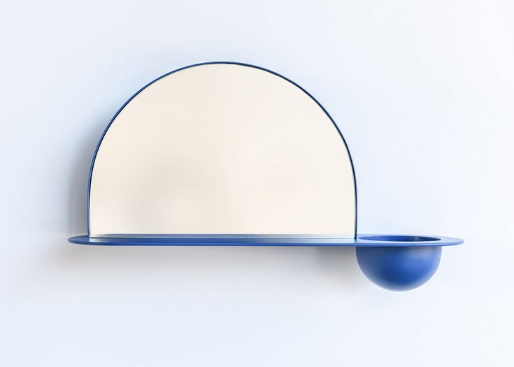A wall-mounted shelf with a semi-circular mirror, a bowl to hold a plant, keys, or change, and a spot behind the mirror to keep your mail or newspapers.