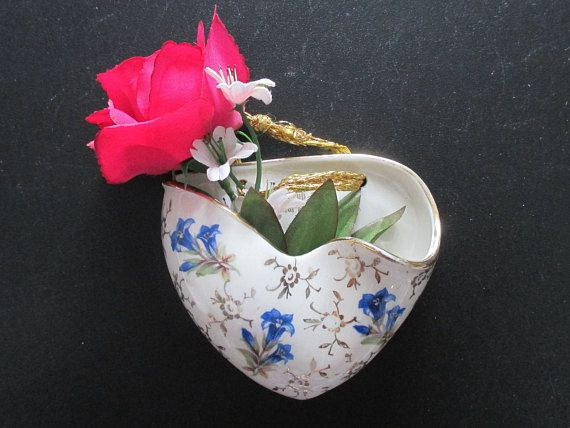 Nothing says I LOVE YOU like a heart! This beautiful and unique heart shaped hanging flower vase is real Bavarian porcelain. It is very colorfully decorated with blue enzian flowers and gold floral touches, as well as a gilt / gold rim. There is a lot of detail in this beautiful porcelain wall vase, and it would make a wonderful focal point in your entryway or in a nook. This Midcentury wall vase is in good vintage condition, with one little flea bite on the front. The vase measures near...