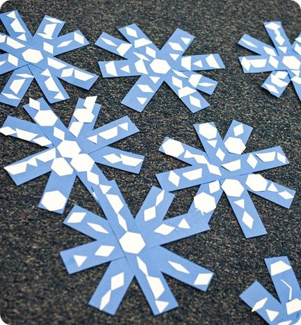Symmetrical snowflakes made from strips of construction paper with added punched-out patterns