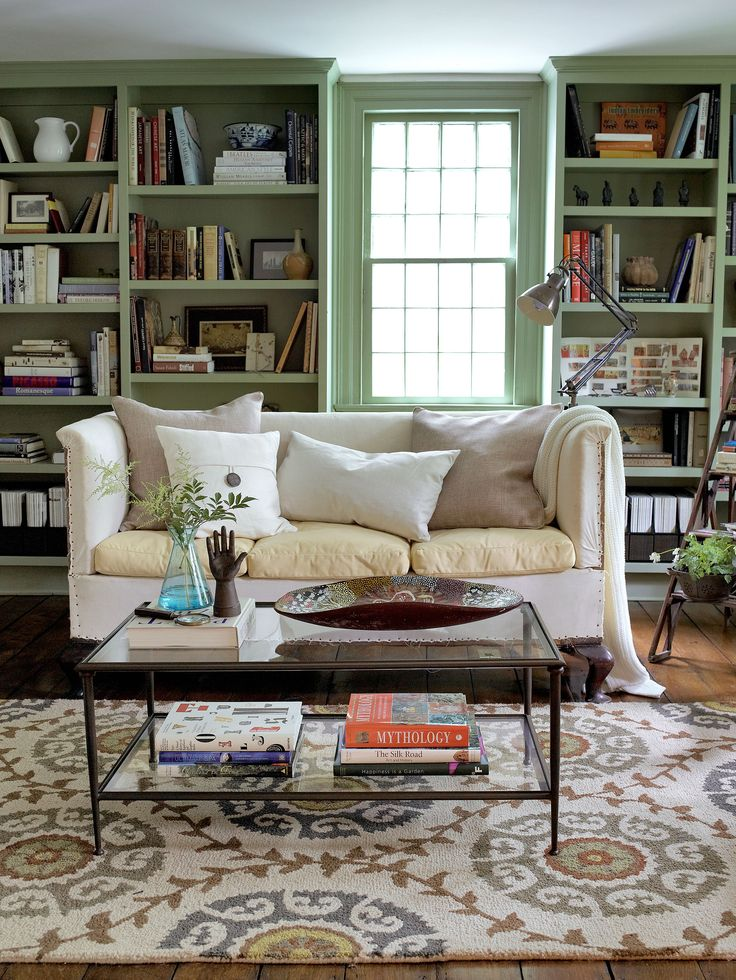 In this photo: The library sofa, a flea-market find, features a mix of muslin upholstery and linen seat covers. The coffee table is from Crate & Barrel. The bookcase is painted Sherwood Green by Benjamin Moore.   - CountryLiving.com