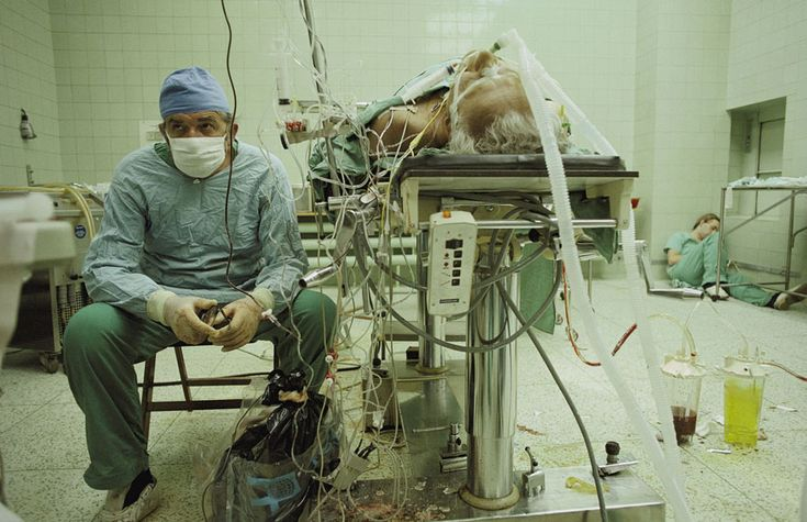 . Cirurgia cardíaca bem-sucedida após 23 horas de trabalho. O assistente do cirurgião descansa no canto.