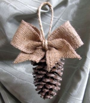 Simple and pretty rustic pine cone Christmas ornament with the perfect burlap bow.