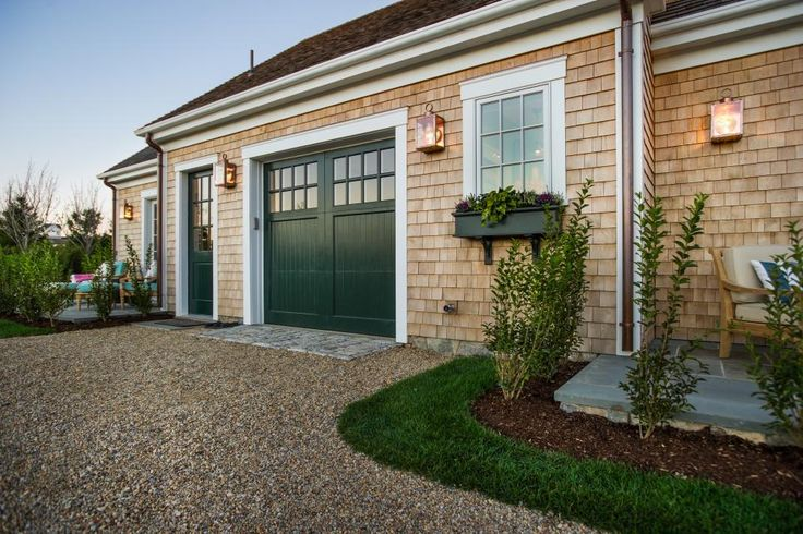 Traditional pea gravel syncs with the surrounding cedar exterior to evoke a charming cottage feel, while a carriage garage door blends tastefully and completes the classic Cape Cod style.