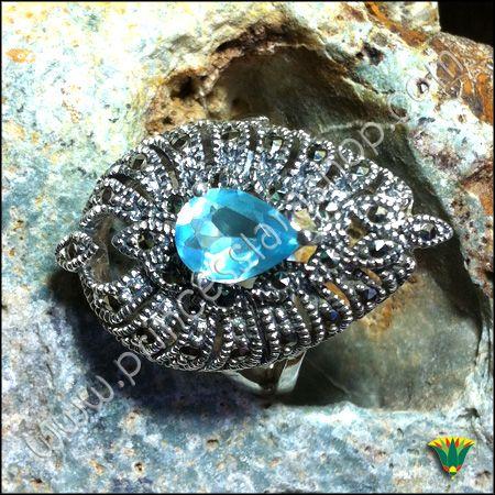 Anillo realizado en plata de ley 925 con piedra semipreciosa de aguamarina y marcasita. El AGUAMARINA es una gema de la familia del berilio que debe su color azul pálido y transparente a los rastros de hierro.Está asociada al mar y, por tanto, al elemento agua, lo cual se dice que proporciona a quien la lleva una gran visión interior (clarividencia).