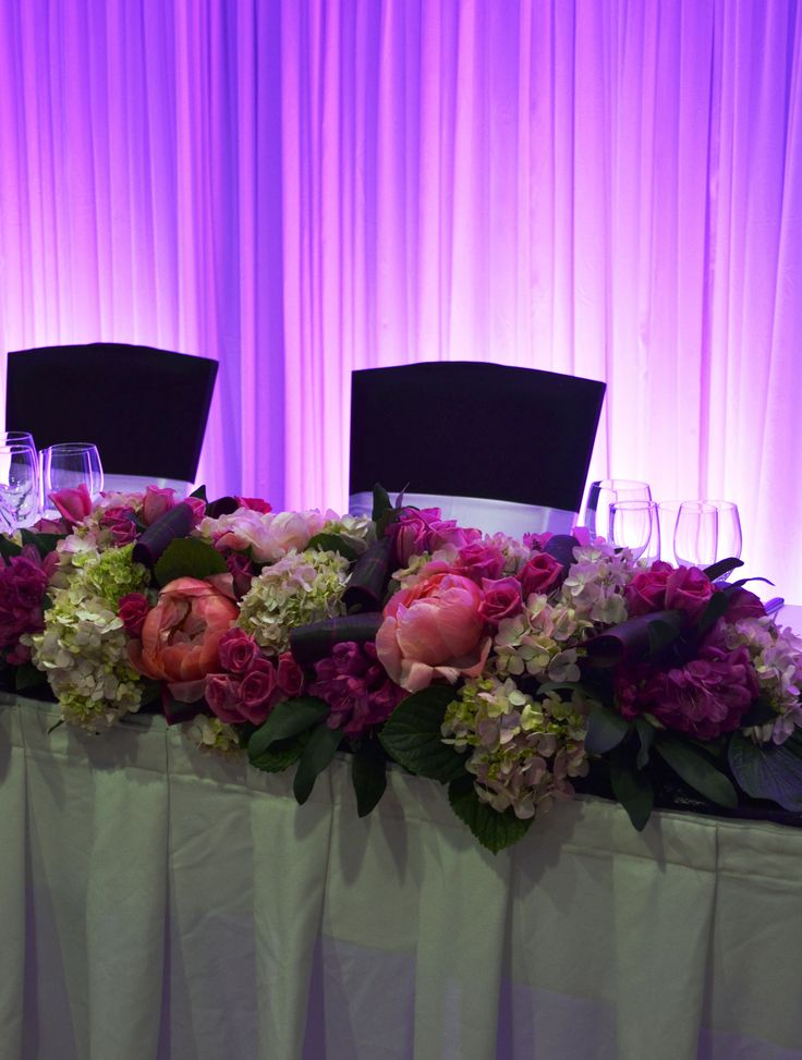 Pink bridal table floral hedge with backdrop lit in pink. Styled by Greenstone Events.