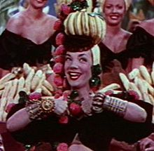 """Carmen Miranda, GCIH (9 February 1909 – 5 August 1955) was a Portuguese-born Brazilian samba singer, dancer, Broadway actress, & film star who was popular in the 1940s and 1950s. After establishing a successful singing and acting career in Brazil, Lee Shubert signed Miranda and her band to a contract in 1939. She made her American stage debut in July 1939, and later moved to Hollywood to pursue a film career.Nicknamed """"The Brazilian B"""