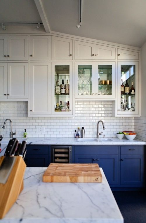 All white, subway tile backsplash, nice contrast with the dark blue cabinets underneath...on a side note, looks like somebody got the wrong knife block, not enough room for their cleaver.