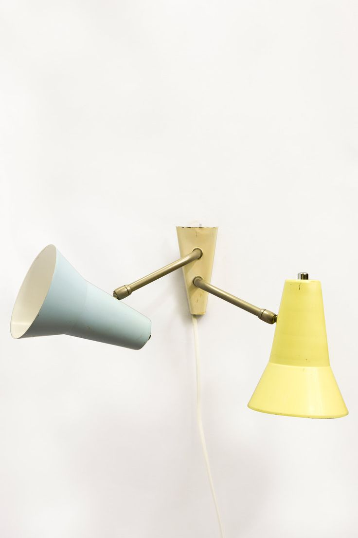 Speels Hala design wandlampje uit de jaren 50. Een blauw en lichtgeel metalen spotje op een chroom sprietje aan een drie hoekig wandplaatje. Leuk voor in de kinderkamer of in een echt 50er jaren interieur.