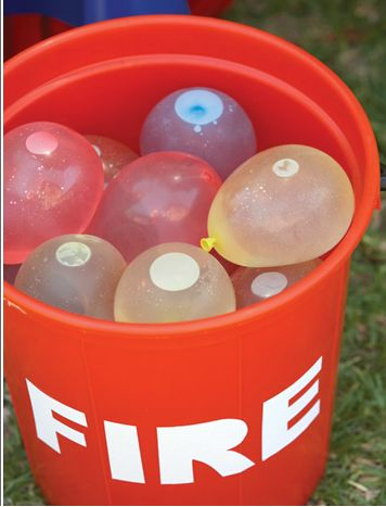 Cute fire theme table, cupcake and water balloon game