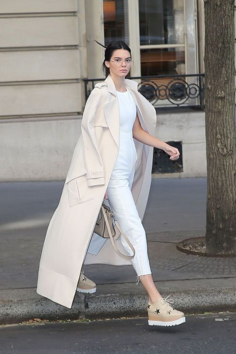 The model steps out off-duty at Paris Fashion Week wearing Garrett Leight glasses, a Sally LaPointe trench coat, and a beige handbag and creepers over a white ASOS jumpsuit.
