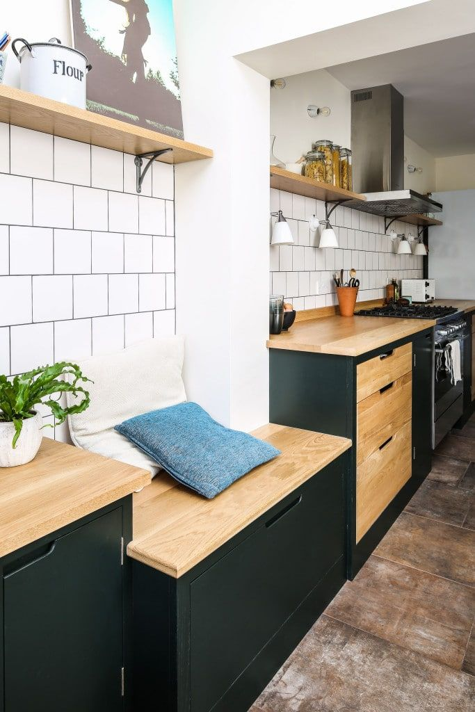 Oak bench seating as part of a run of flat panel kitchen cabinetry. The cabinetry is birch with solid oak worktop. It's painted in Little Greene Obisidian Green. The white square tiles break up the area between the open shelving and base cabinetry. The bench seating helps transitions the space from kitchen to living and office area. Flooring is from Mandarin Stone. Wall lights from Original BTC.